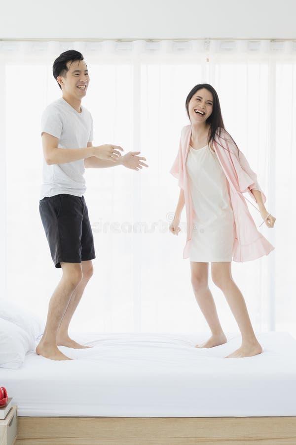 Прекрасные азиатские пары скача на кровать в спальне стоковая фотография