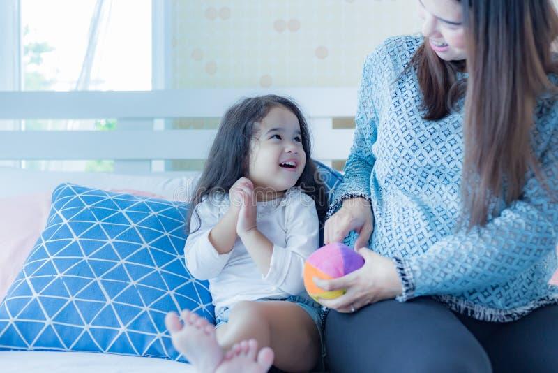 Прекрасные маленькие азиатские взгляды девушки или дочери на маме с любовью Любов ребенка дошкольного возраста оставаясь с матерь стоковое изображение rf