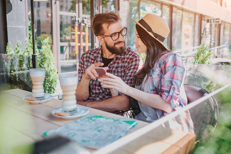 Прекрасные пары сидят совместно и смотрят один другого Она держит телефон в руках Он указывает на его Они усмехаются друг к другу стоковая фотография rf