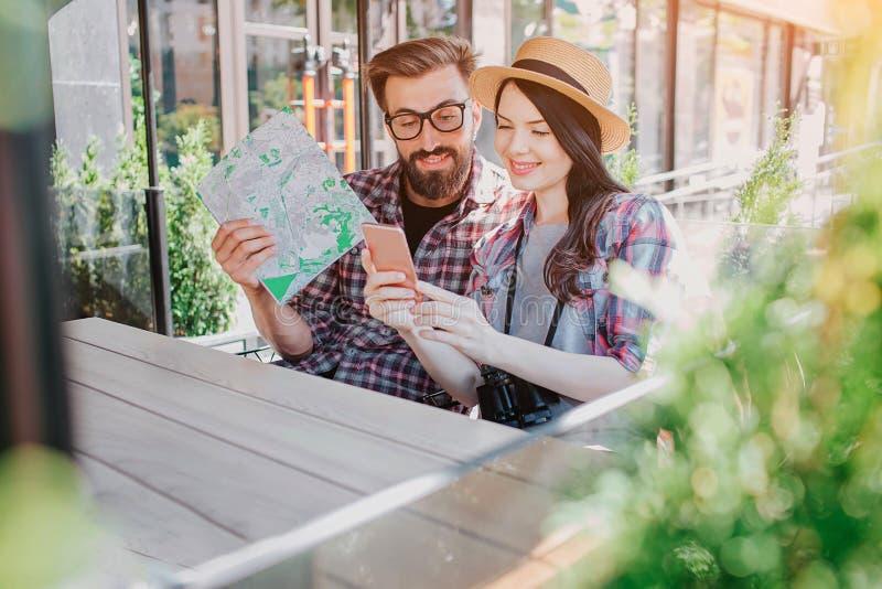 Прекрасные пары trvellers сидя и смотря владения женщины телефона в руках Они усмехаются Молодой человек держит карту в руке стоковое изображение