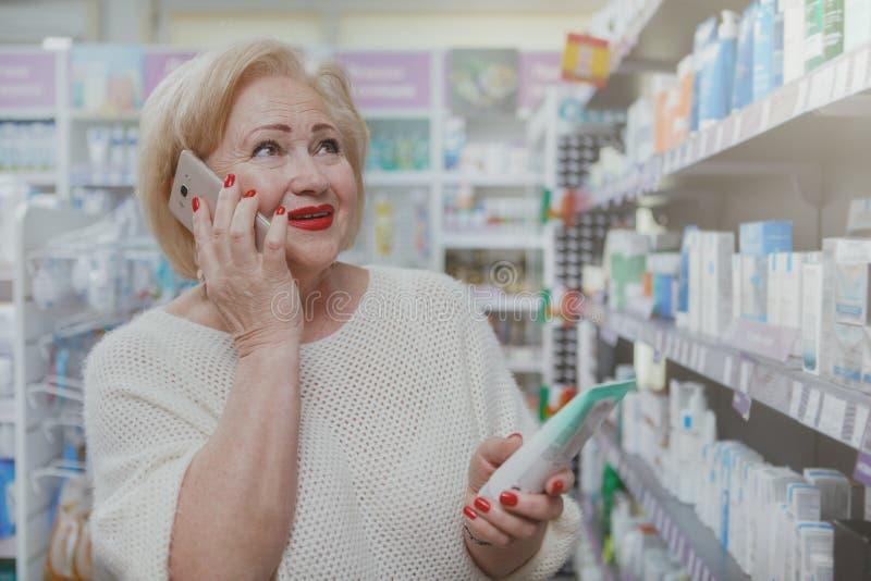 Прекрасные старшие покупки женщины на аптеке стоковые фотографии rf