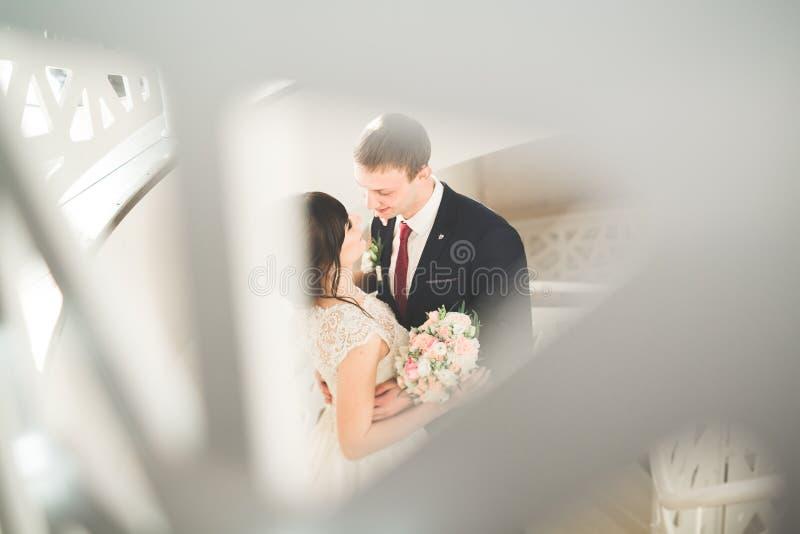 Прекрасные счастливые пары свадьбы, невеста с длинным белым платьем представляя в красивом городе стоковые изображения rf