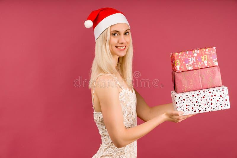 Прекрасный атлетик-трансгендер в новогодней шляпе и белом платье, держит в руках подарки Празднование Рождества или нового стоковые изображения