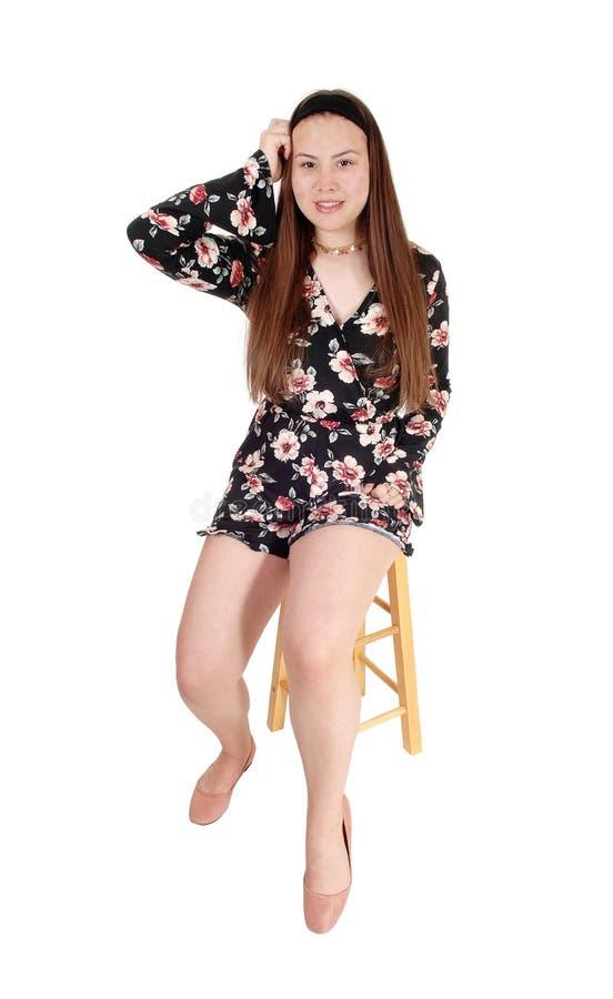 Прекрасный девочка-подросток сидя на руке стула одного на голове стоковые фото