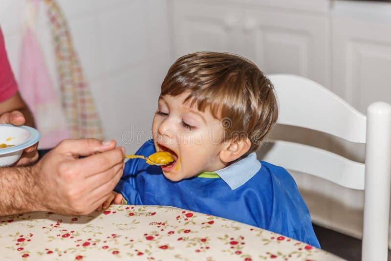 Прекрасный маленький белокурый мальчик ест пюре моркови с много желания стоковое фото rf