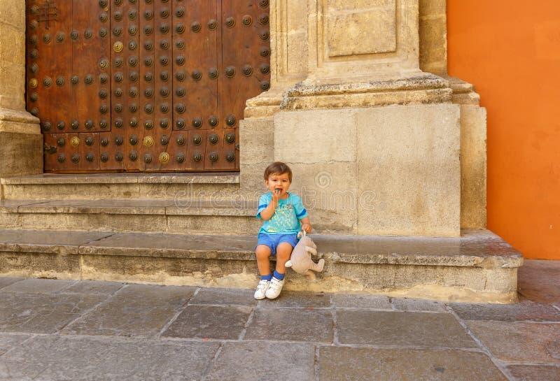 Прекрасный ребенок сидя с его куклой, рядом со старым зданием стоковое изображение rf