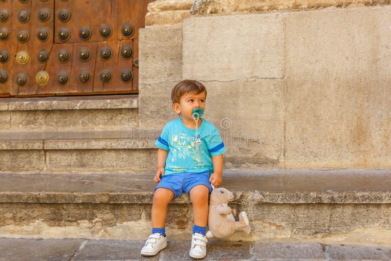 Прекрасный ребенок сидя с его куклой, рядом со старым зданием стоковые изображения