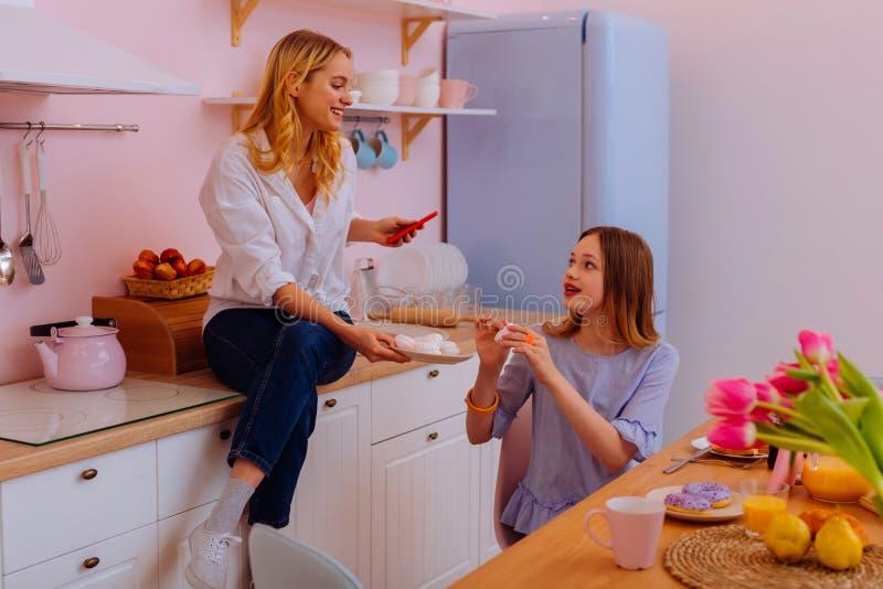 2 прекрасных симпатичных сестры деля помадки во время завтрака стоковые изображения rf
