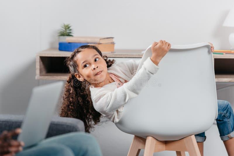 прелестная Афро-американская девушка сидя на стуле и смотря отца сидя с ноутбуком стоковые фотографии rf
