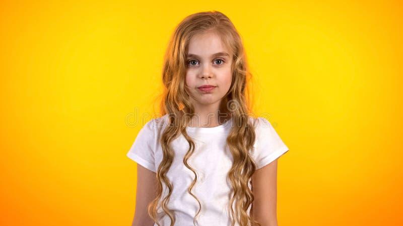 Прелестная белокурая девушка изолированная на оранжевой предпосылке смотря к камере, детстве стоковая фотография rf