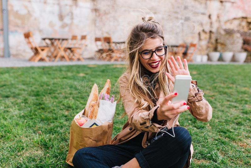 Прелестная белокурая девушка с продуктовой сумкой сидя на лужайке разговаривая с друзьями видео- звонком Молодая белокурая женщин стоковое фото