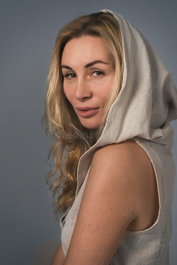 Прелестная белокурая женщина в безрукавное hoody против серой предпосылки стоковые фото