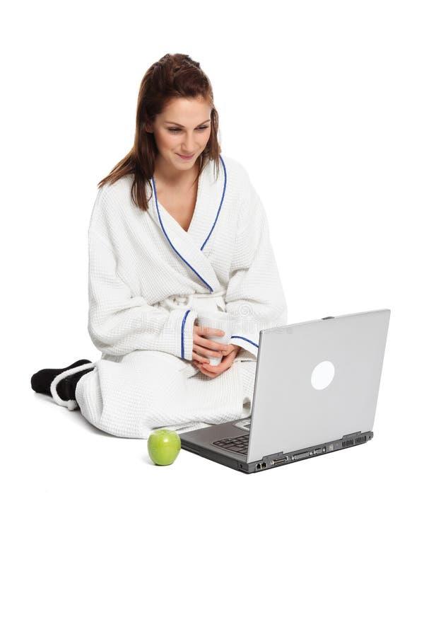 Прелестная женщина сидя вниз наблюдающ ее экран компьютера стоковое фото