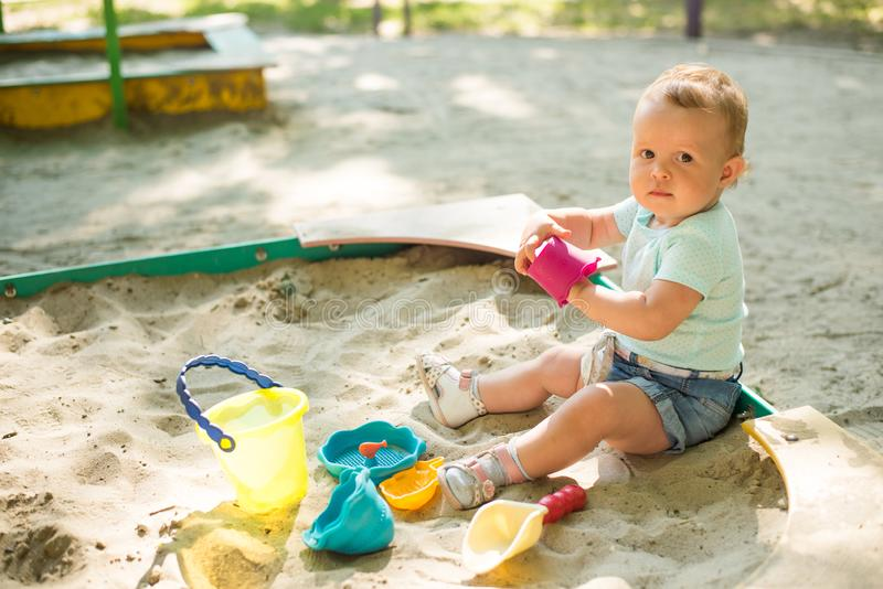 Прелестная игра младенца с песком в ящике с песком на спортивной площадке стоковые изображения rf
