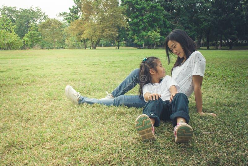 Прелестная концепция: Счастье женщины и ребенка обнимая и чувствуя усмехаясь в парке стоковые изображения