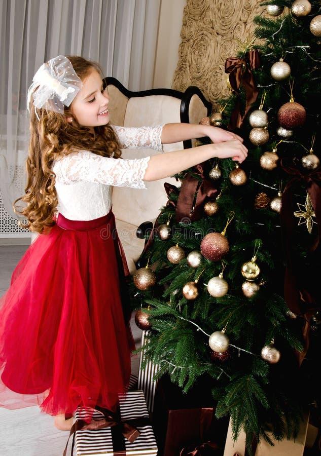 Прелестная маленькая девочка в платье принцессы вися вверх шарики дальше стоковая фотография