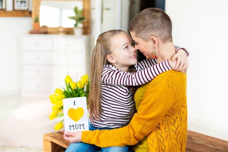 Прелестная маленькая девочка давая ее маму, молодой онкологический больного, домодельный Я ЛЮБЛЮ поздравительную открытку МАМЫ Сч стоковые изображения rf