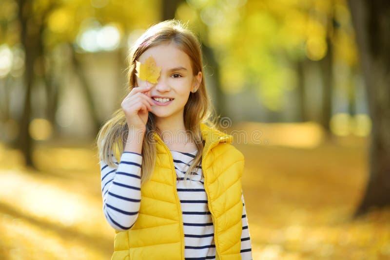 Прелестная маленькая девочка имея потеху на красивый день осени Счастливый ребенок играя в парке осени Листопад схода ребенк желт стоковая фотография