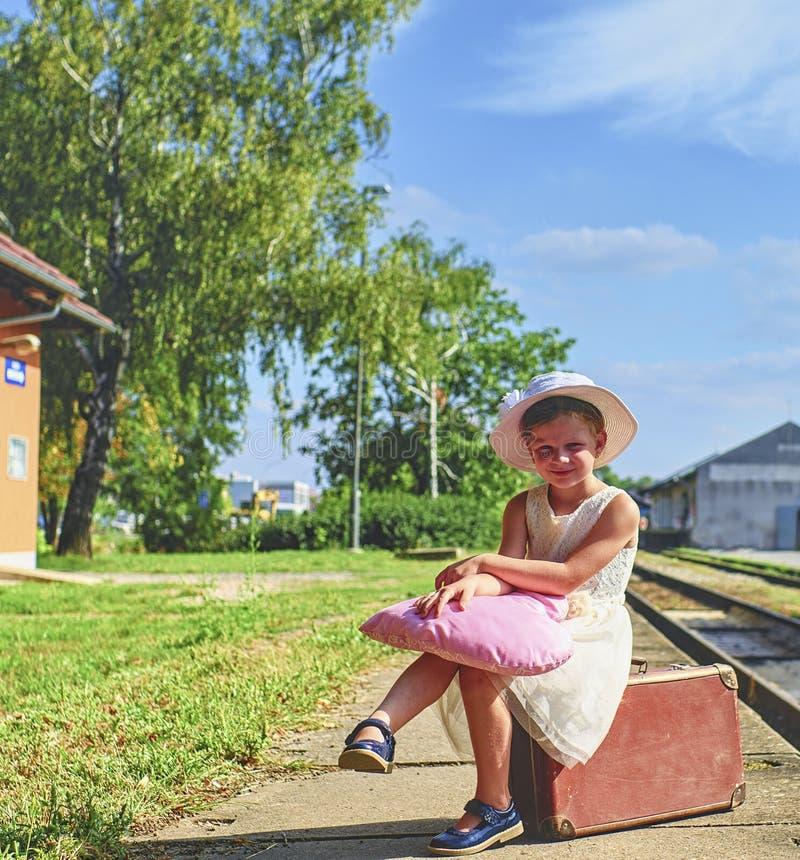 Прелестная маленькая девочка на железнодорожном вокзале, ждать поезд с винтажным чемоданом Путешествовать, праздник и chilhood стоковое фото rf
