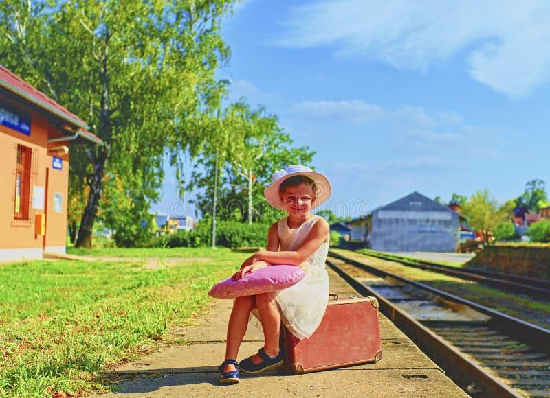 Прелестная маленькая девочка на железнодорожном вокзале, ждать поезд с винтажным чемоданом Путешествовать, праздник и chilhood стоковая фотография