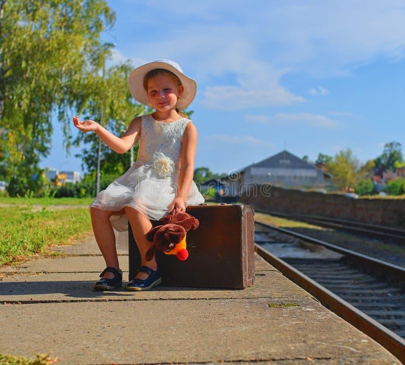 Прелестная маленькая девочка на железнодорожном вокзале, ждать поезд с винтажным чемоданом Путешествовать, праздник и chilhood стоковая фотография rf