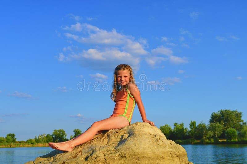 Прелестная маленькая девочка сидя на большом камне в озере на горячий летний день Ребенок одетый в купальнике Лето и счастливое стоковая фотография rf