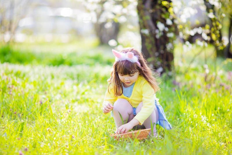 Прелестная маленькая девочка сидя на зеленой траве играя в саде на охоте пасхального яйца стоковое фото rf