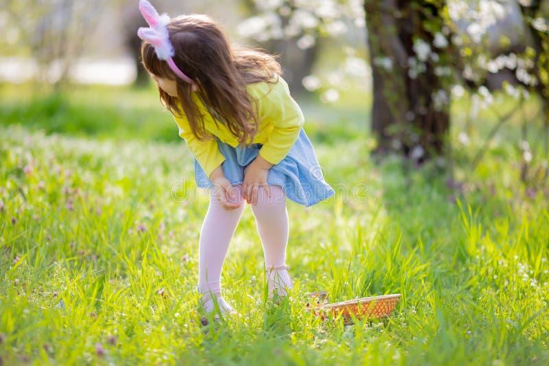 Прелестная маленькая девочка сидя на зеленой траве играя в саде на охоте пасхального яйца стоковые изображения