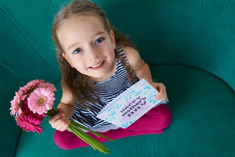 Прелестная маленькая девочка сидя на кресле, смотря вверх и держа букет розовой карточки дня маргариток gerbera и ` s матери стоковые фотографии rf