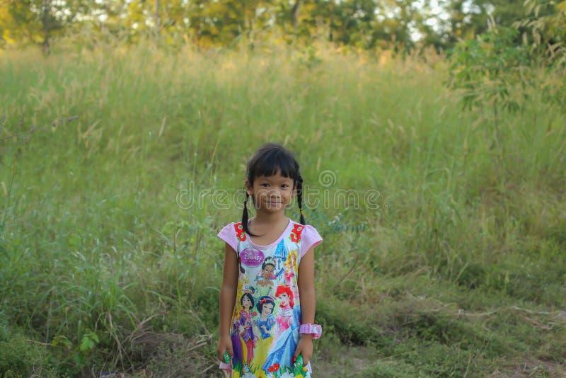 Прелестная маленькая девочка смеясь в луге - счастливая девушка на заходе солнца стоковое фото rf