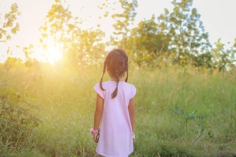 Прелестная маленькая девочка смеясь в луге - счастливая девушка на заходе солнца стоковое изображение rf