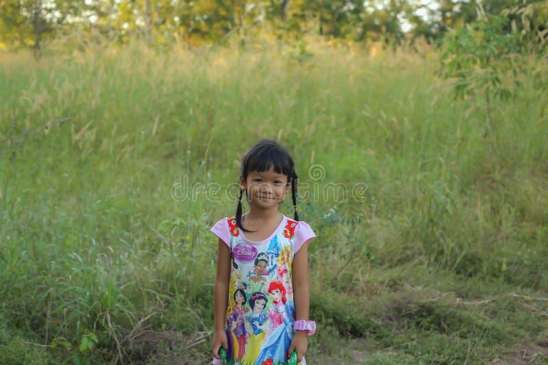 Прелестная маленькая девочка смеясь в луге - счастливая девушка на заходе солнца стоковые фотографии rf