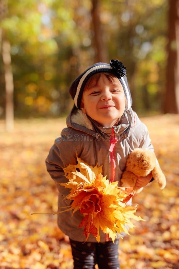 Прелестная маленькая девочка outdoors на красивом дне осени стоковые изображения rf