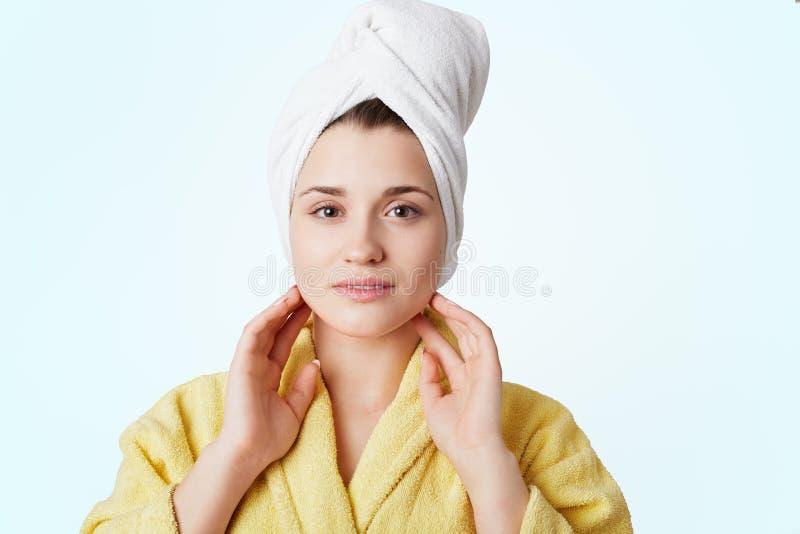 Прелестная молодая симпатичная женщина в купальном халате и полотенце, имеет ливень, представляет против белой предпосылки, был р стоковая фотография rf