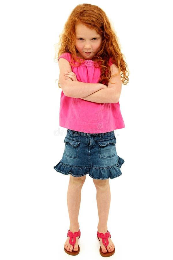 Прелестная сердитая маленькая девочка при пересеченные рукоятки стоковые изображения