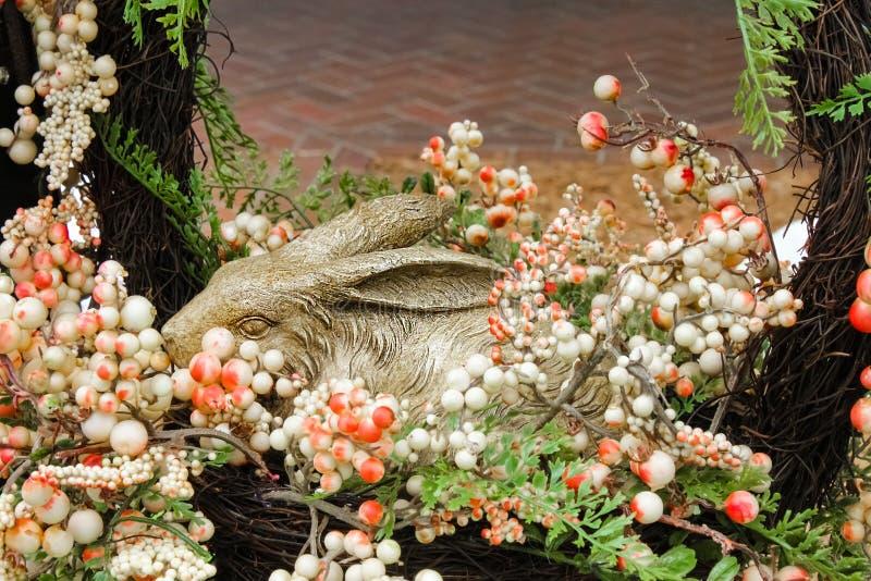 Прелестная скульптура кролика в венке при мягкий пузырь смотря цветки совсем вокруг его - селективный фокус и конец вверх стоковые фотографии rf