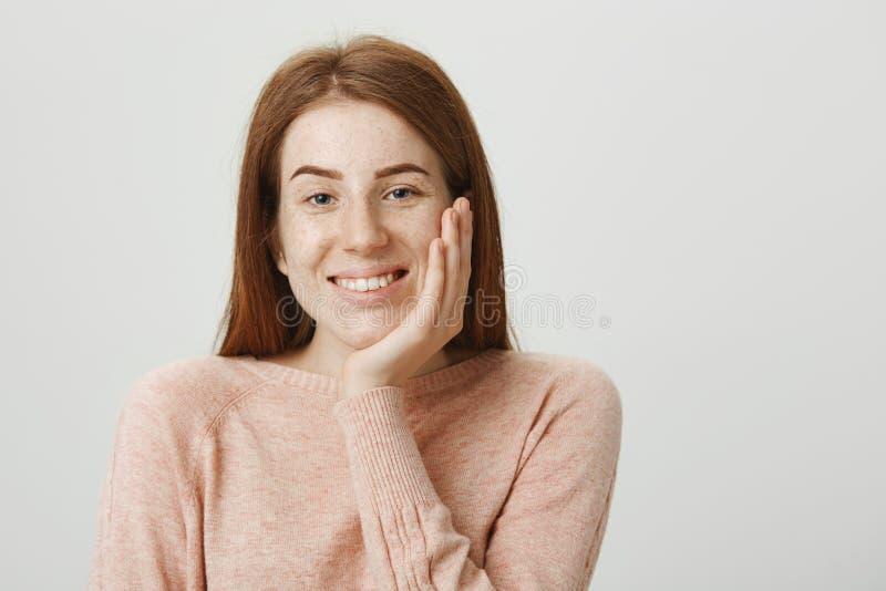 Прелестная студентка redhead полагаясь в наличии пока усмехающся, выражающ положительные эмоции, слушая к кто-нибудь стоковые фото
