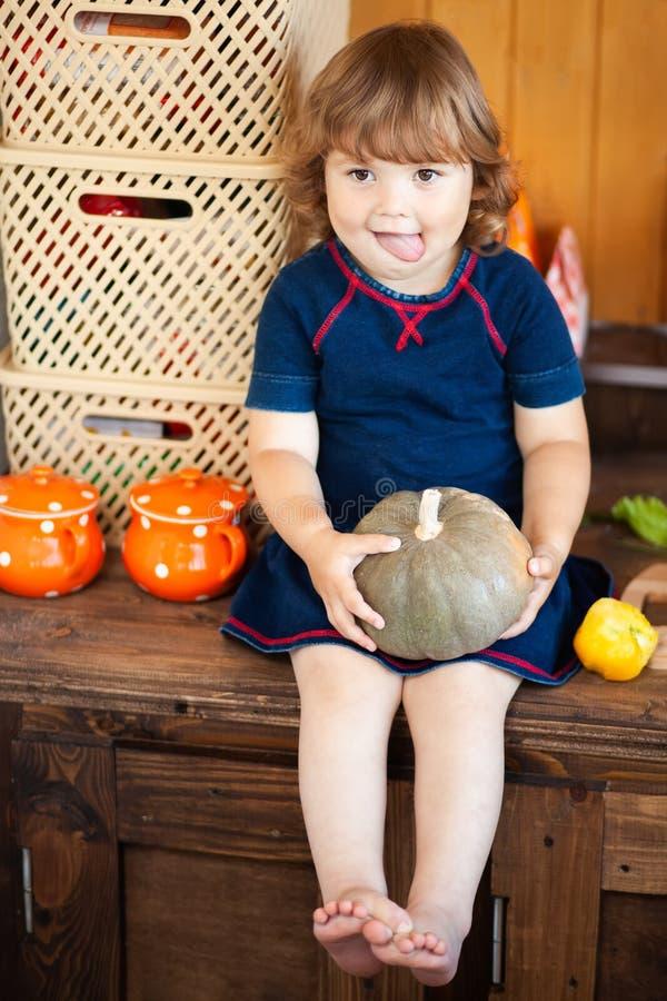 Прелестная счастливая девушка малыша сидя в кухне внутри помещения, держащ тыкву и усмехаться стоковая фотография rf