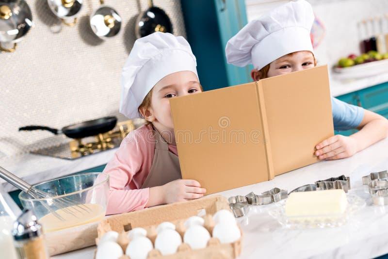 прелестные дети в шляпах шеф-повара держа поваренную книгу и смотреть стоковая фотография rf
