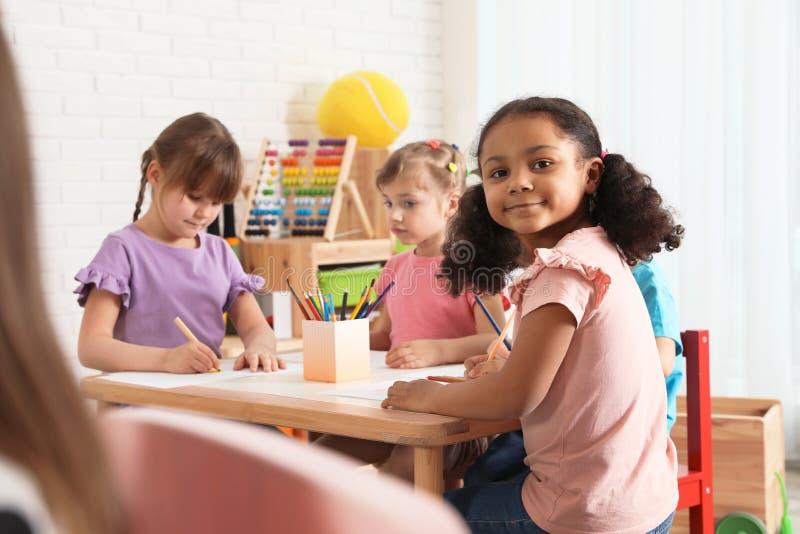 Прелестные дети рисуя совместно на таблице Деятельности при playtime детского сада стоковое фото