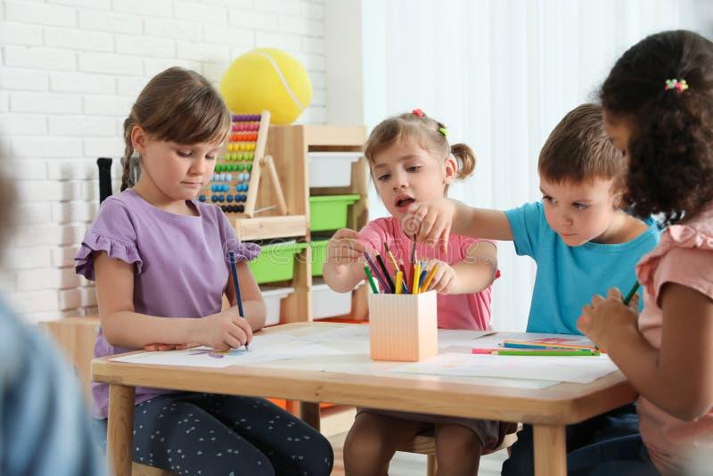 Прелестные дети рисуя совместно на таблице Деятельности при playtime детского сада стоковая фотография rf