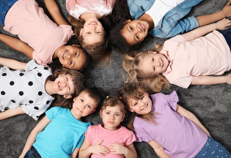 Прелестные маленькие дети лежа на поле совместно внутри помещения Деятельности при playtime детского сада стоковые изображения rf