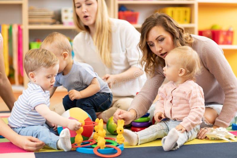 Прелестные малыши играя с красочными игрушками и матерями в комнате питомника стоковые фотографии rf