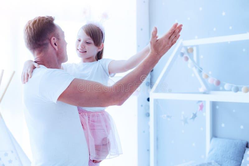 Прелестные танцы маленькой девочки с заботливым отцом стоковая фотография