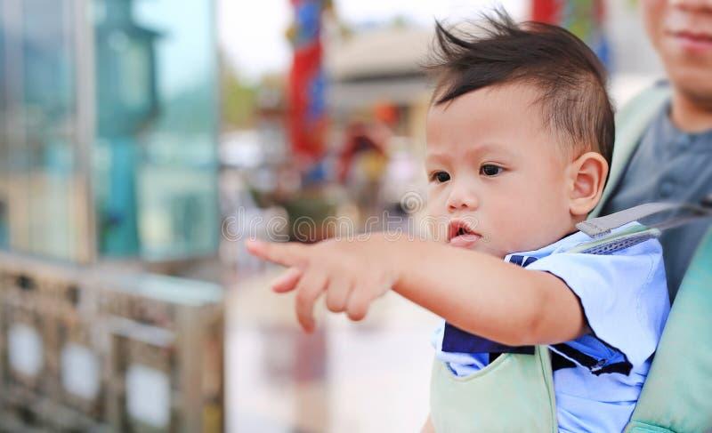 Прелестный маленький ребенок указывая что-то с отцом носит hipseat на открытом воздухе r стоковое изображение