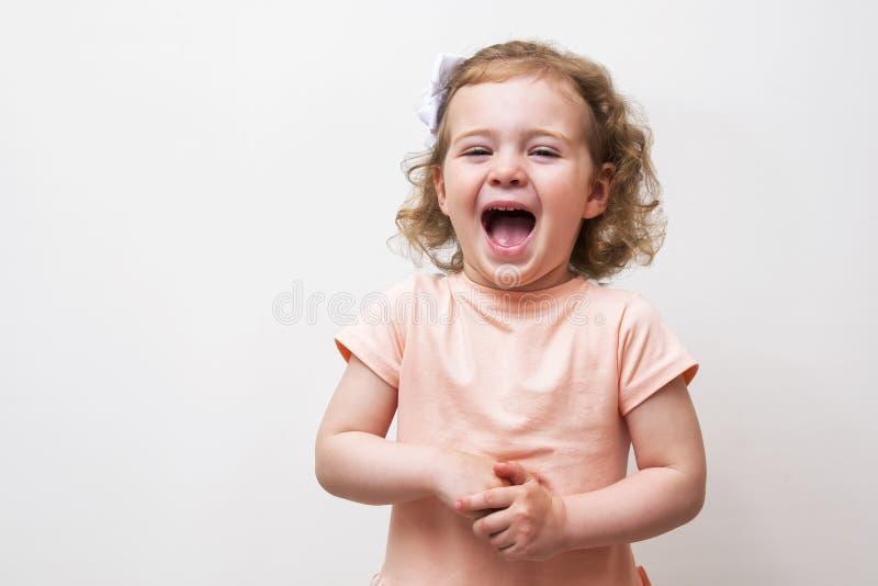 Прелестный маленький ребёнок смеясь над и играя в студии, изолированной на белой предпосылке стоковые фотографии rf