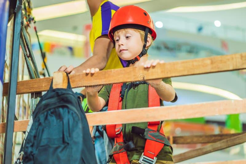 Прелестный мальчик наслаждаясь его временем во взбираясь парке приключения в торговом центре стоковые изображения