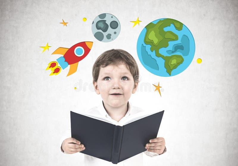 Прелестный мальчик с книгой, космический полет стоковая фотография