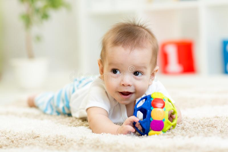 Прелестный младенец имея потеху с игрушкой на уютном половике Счастливый жизнерадостный ребенк играя на поле стоковое фото rf