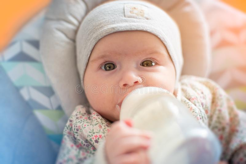 Прелестный ребенок выпивает молоко формулы от бутылки стоковое изображение